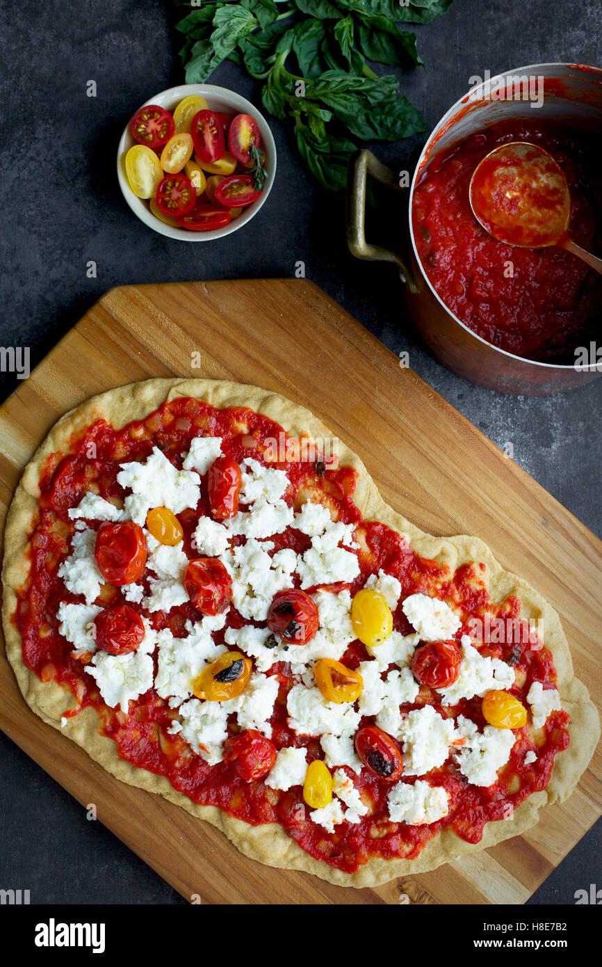 Geröstete Tomaten Pizza mit einer dünnen Olivenöl Crackerkruste.  Fotografiert auf schwarz/grau Hintergrund Stockbild