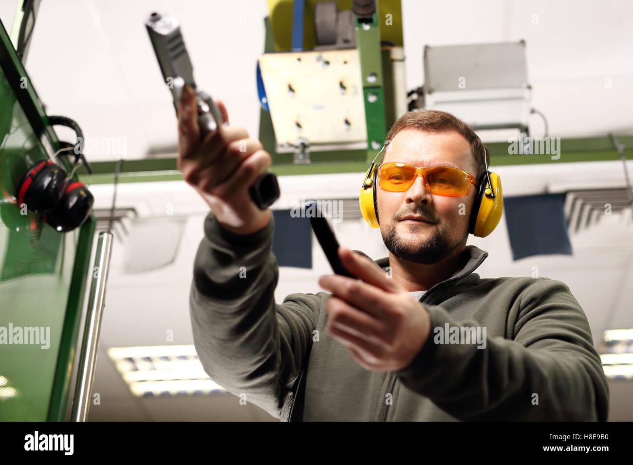 Der Mann an den Dreharbeiten lädt Pistole Stockbild