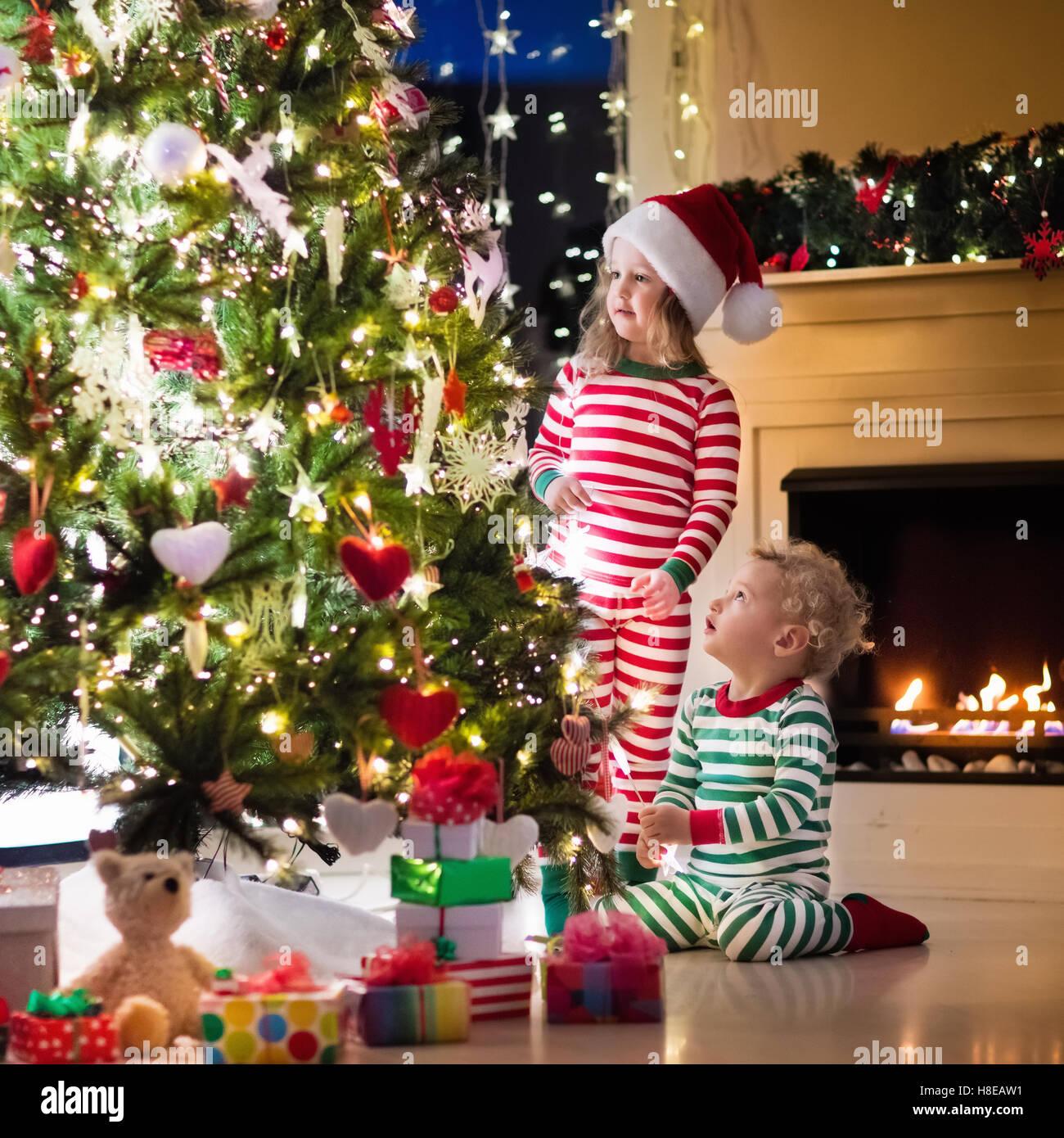 Familie am Heiligen Abend am Kamin. Kinder Weihnachten Geschenke zu ...