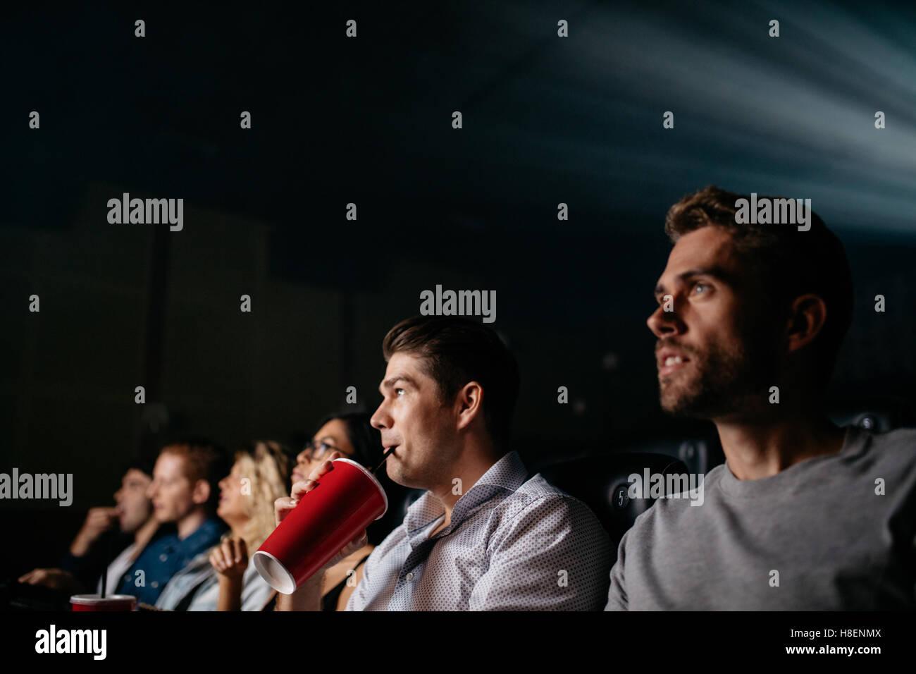 Junger Mann mit Softdrink und Film mit Freunden im Kinosaal. Gruppe von Menschen im Kino. Stockbild