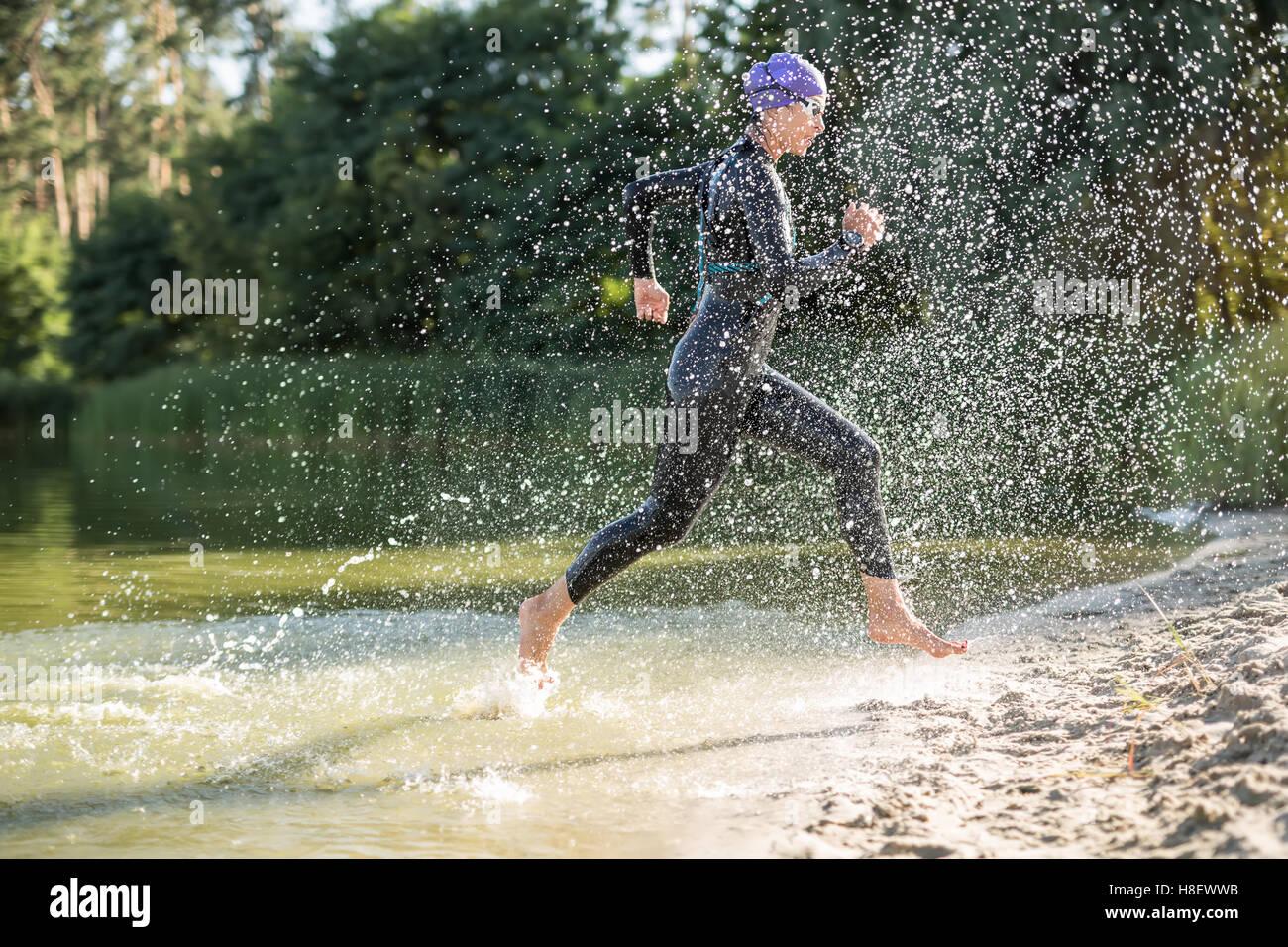 Sportliche Mädchen läuft am Wasser Stockbild
