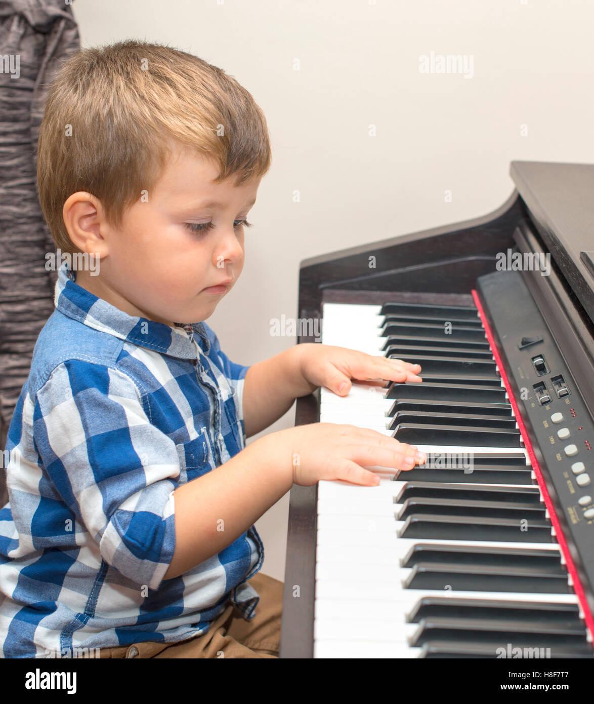 wenig fröhlicher Junge spielt Klavier zu Hause Stockbild