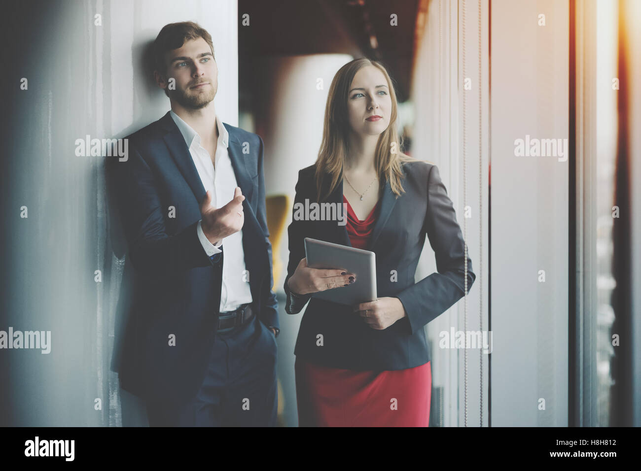 Gruppe von Geschäftsleuten: Mann in formellen Anzug und Frau im roten Kleid und Jacke Holding Tablet zeigt Stockbild