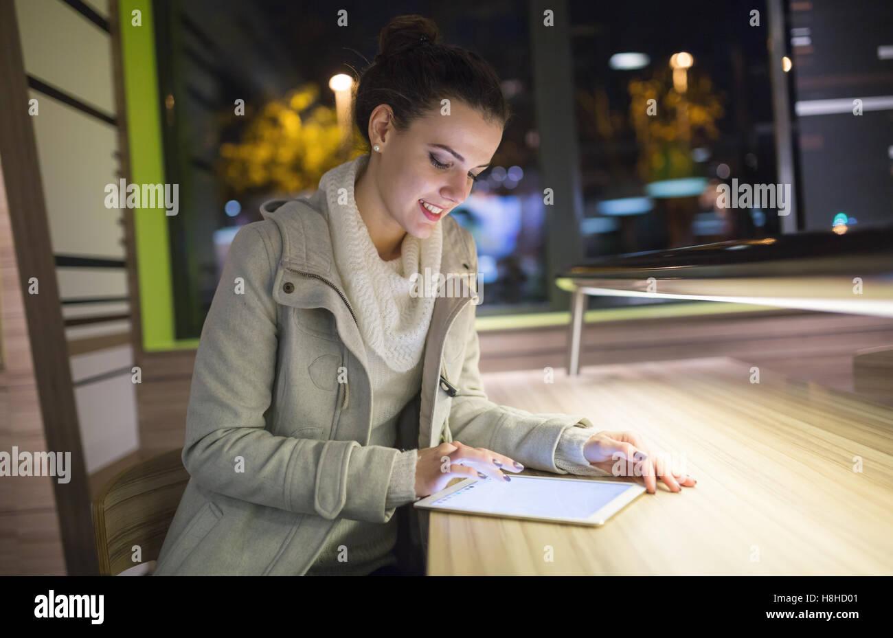 Brünette Frau mit Tablet nach der Arbeit Stockbild