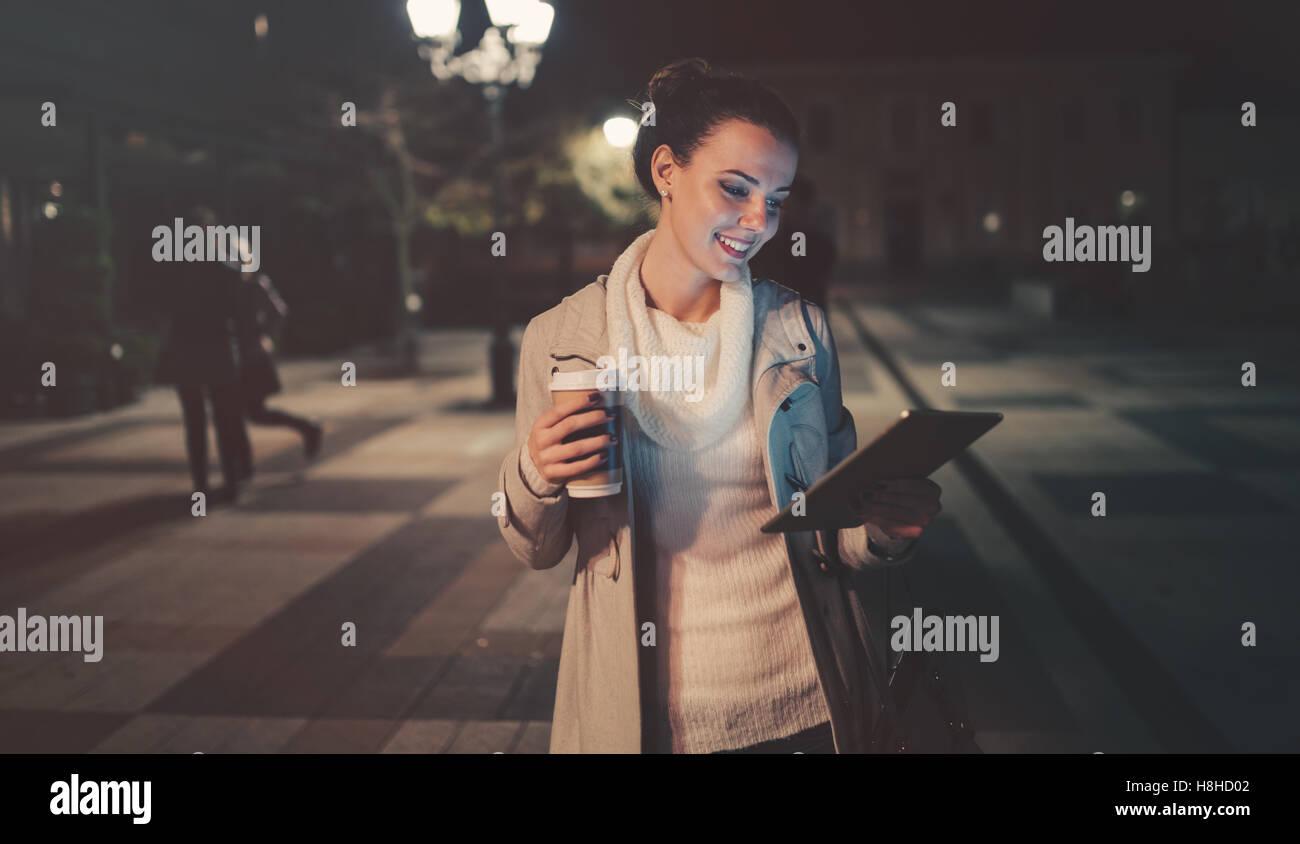 Brünette Frau mit Tablet nach der Arbeit und Kaffee trinken Stockbild