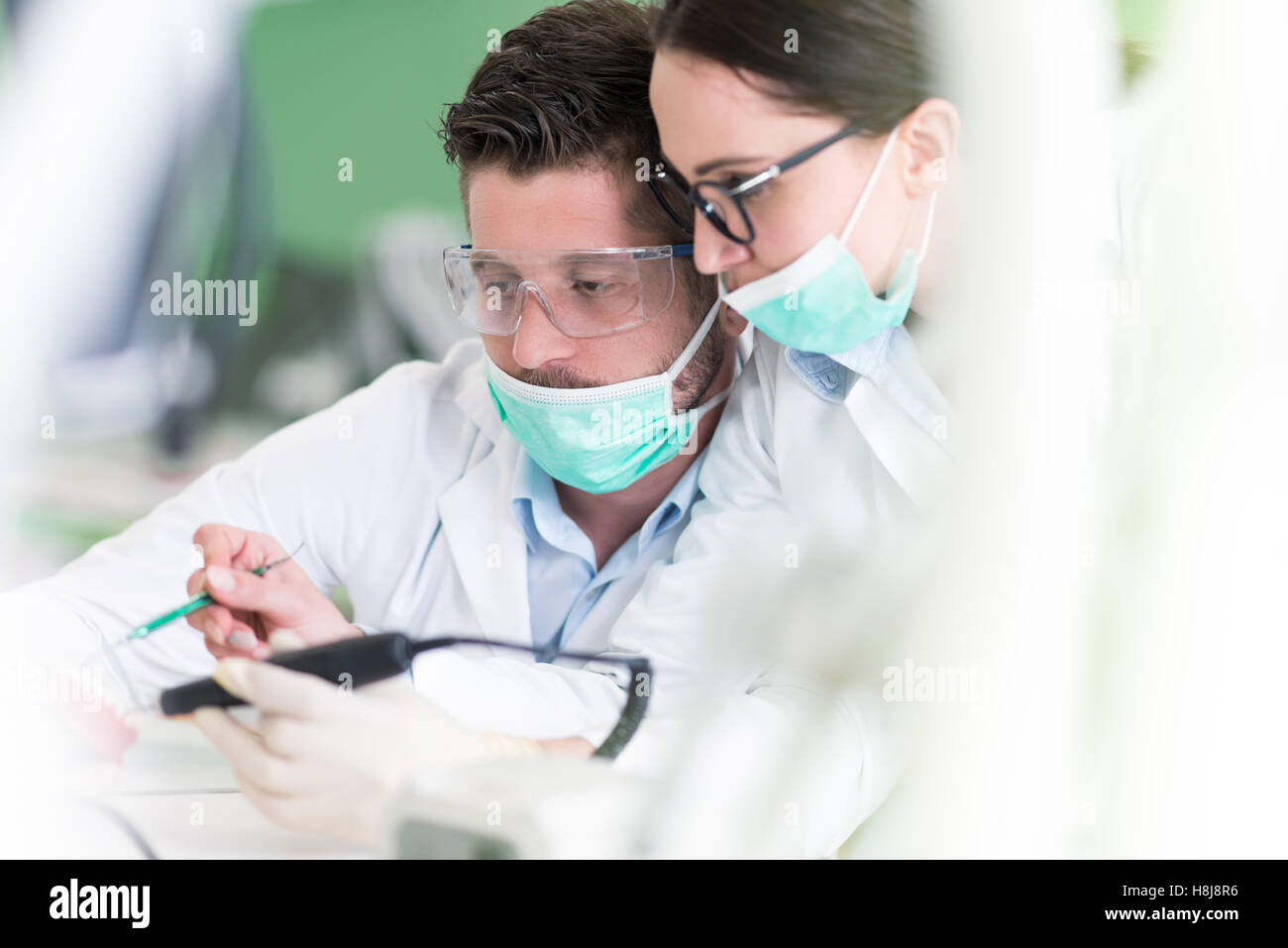 Beschäftigt junge Zahnmedizin-Studenten, die Arbeiten sorgfältig auf ...