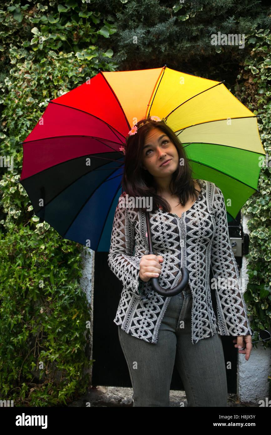 mädchen spielen mit einem regenbogen regenschirm im garten