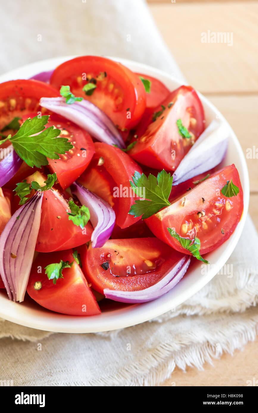 Tomatensalat mit Zwiebeln, Petersilie und Pfeffer in Schüssel - gesunde vegetarische vegane Lebensmittel Vorspeise Stockfoto