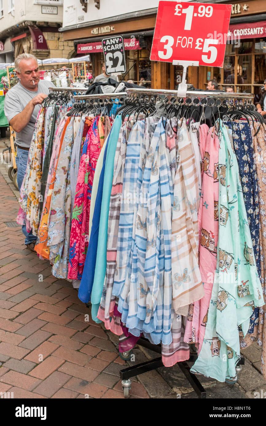 Ein Händler, rauchte eine Zigarette, die Vermittlung von bunten Schals auf Schienen in den Straßenmarkt Stockbild