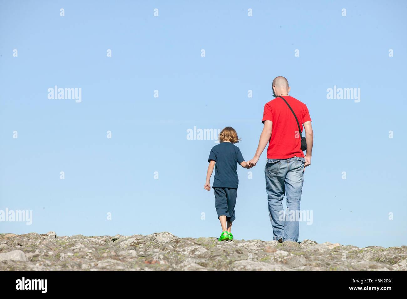 Vater mit Sohn (14-15) Hand in Hand Stockbild