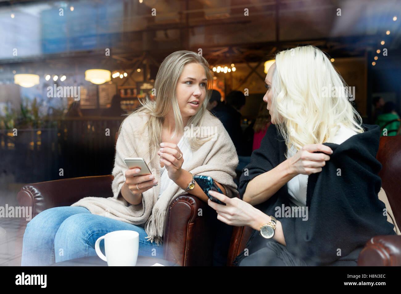 Junge Frauen, die Benutzung von Mobiltelefonen im café Stockbild