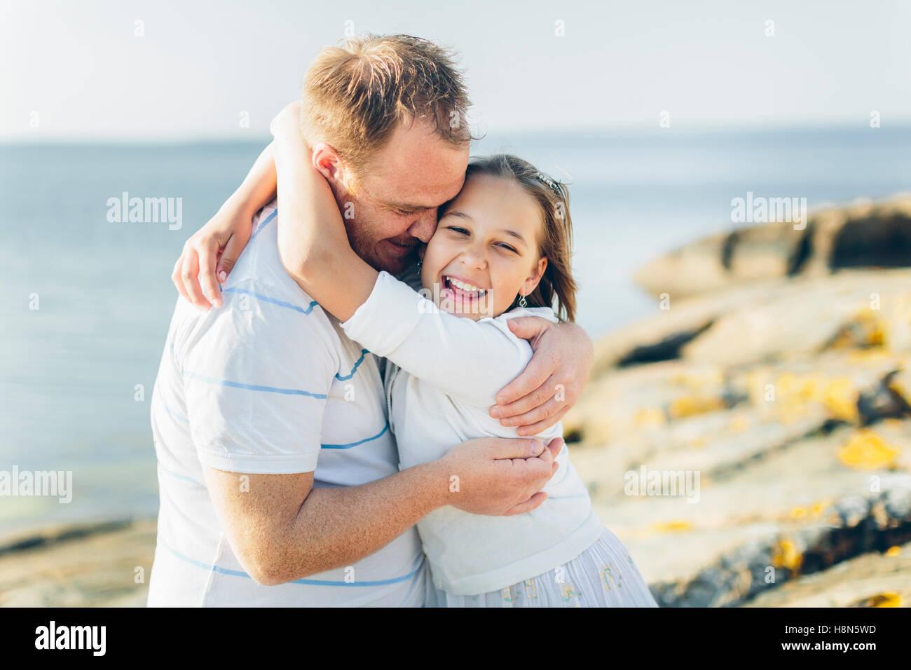 Mann umarmt Mädchen (10-11) Stockbild