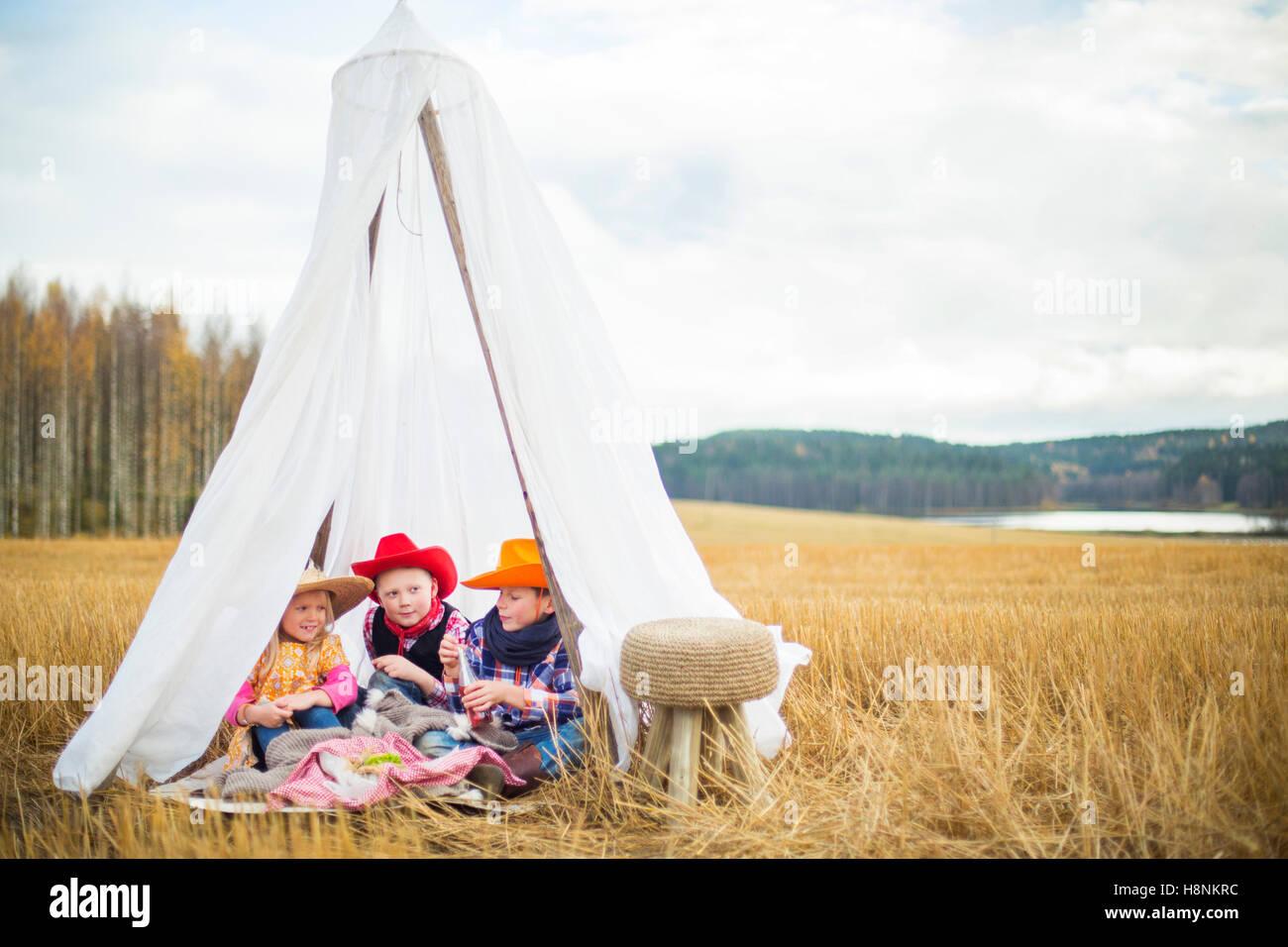 Kinder (8-9) tragen Cowboyhüte sitzen im Zelt Stockbild