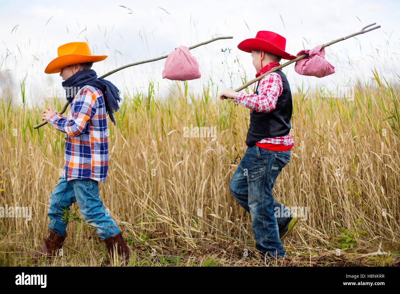 Jungen (8-9) verkleidete sich als Cowboys zu Fuß in Feld Stockbild