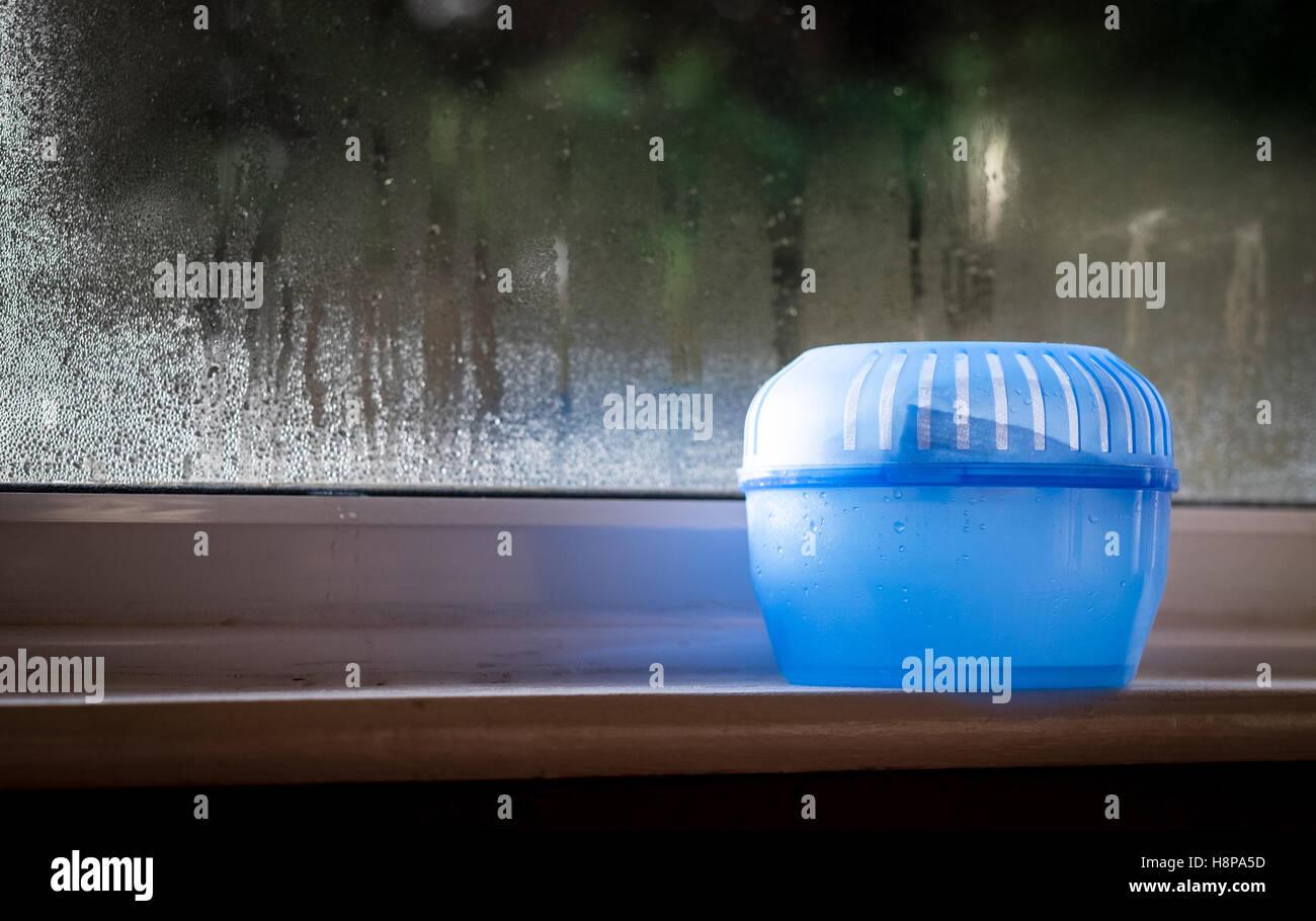 Kunststoff Feuchtigkeit Absorber Wasserabscheider auf einer Fensterbank mit Kondenswasser am Fenster hinter Stockbild