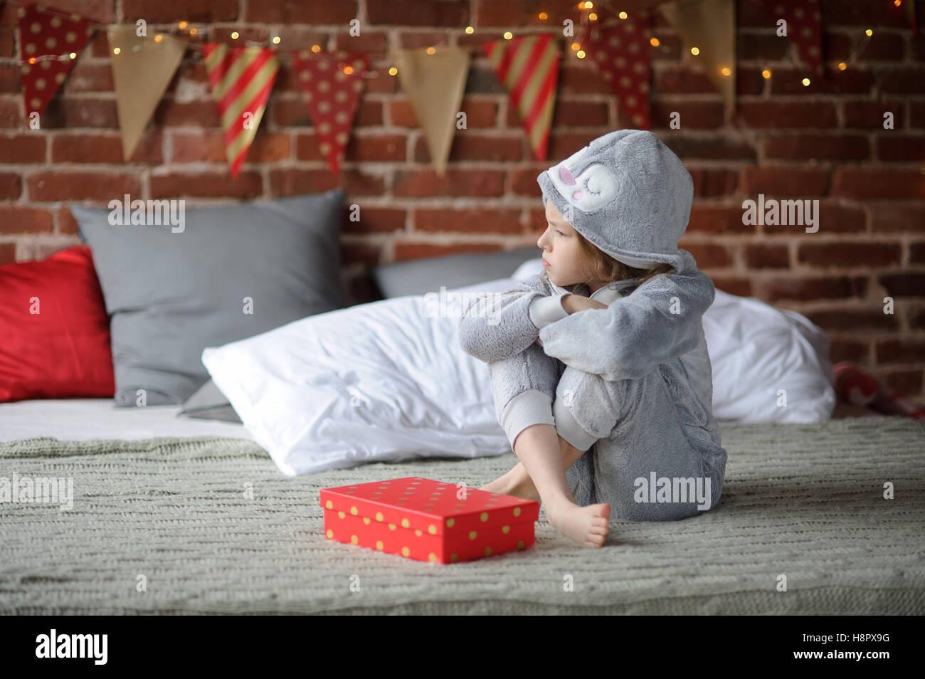 Kleines Mädchen in einem Schlafanzug sitzt alleine auf einem großen ...