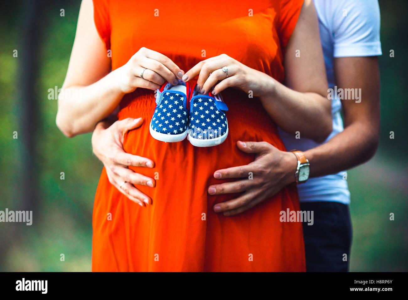 Schwangere Frau und ihr Mann hält Babyschuhe Stockbild