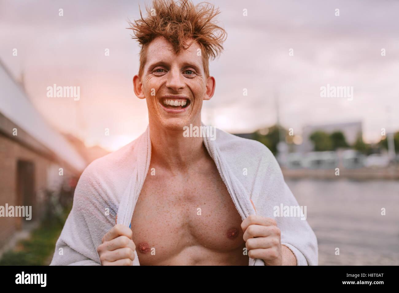 Porträt von gut aussehenden jungen Mann in Blick in die Kamera und lächelnd Handtuch gewickelt. Fröhliche Stockbild