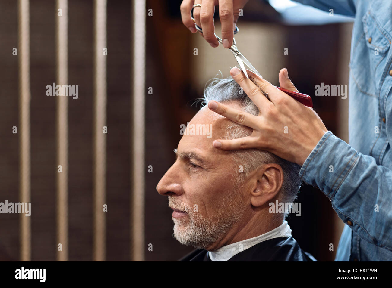 Alten Herrn während Haarschnitt im barbershop Stockbild