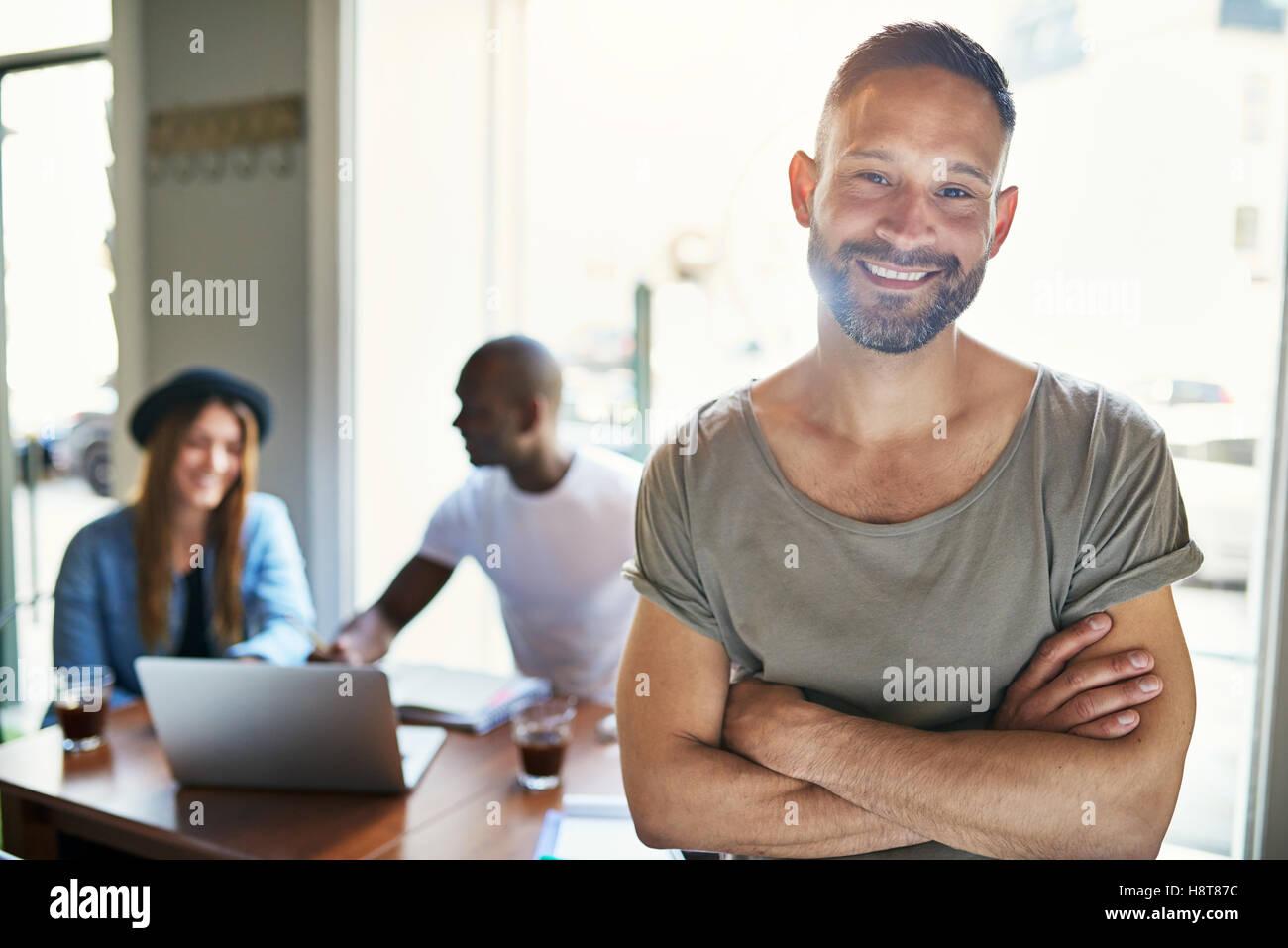 Bärtiger Mann in Kurzarm Shirt schön Lächeln und gefaltet Arme stehen im Café mit Kunden im Stockbild