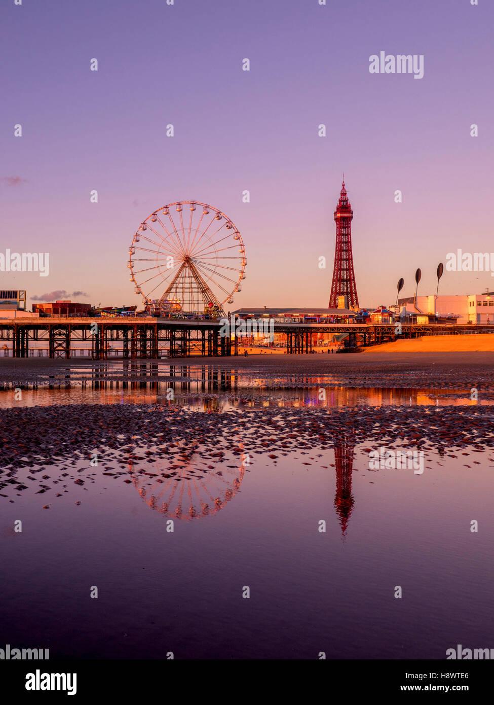 Blackpool Tower und Central Pier mit Spiegelung im Wasser am Strand bei Sonnenuntergang, Lancashire, UK. Stockbild