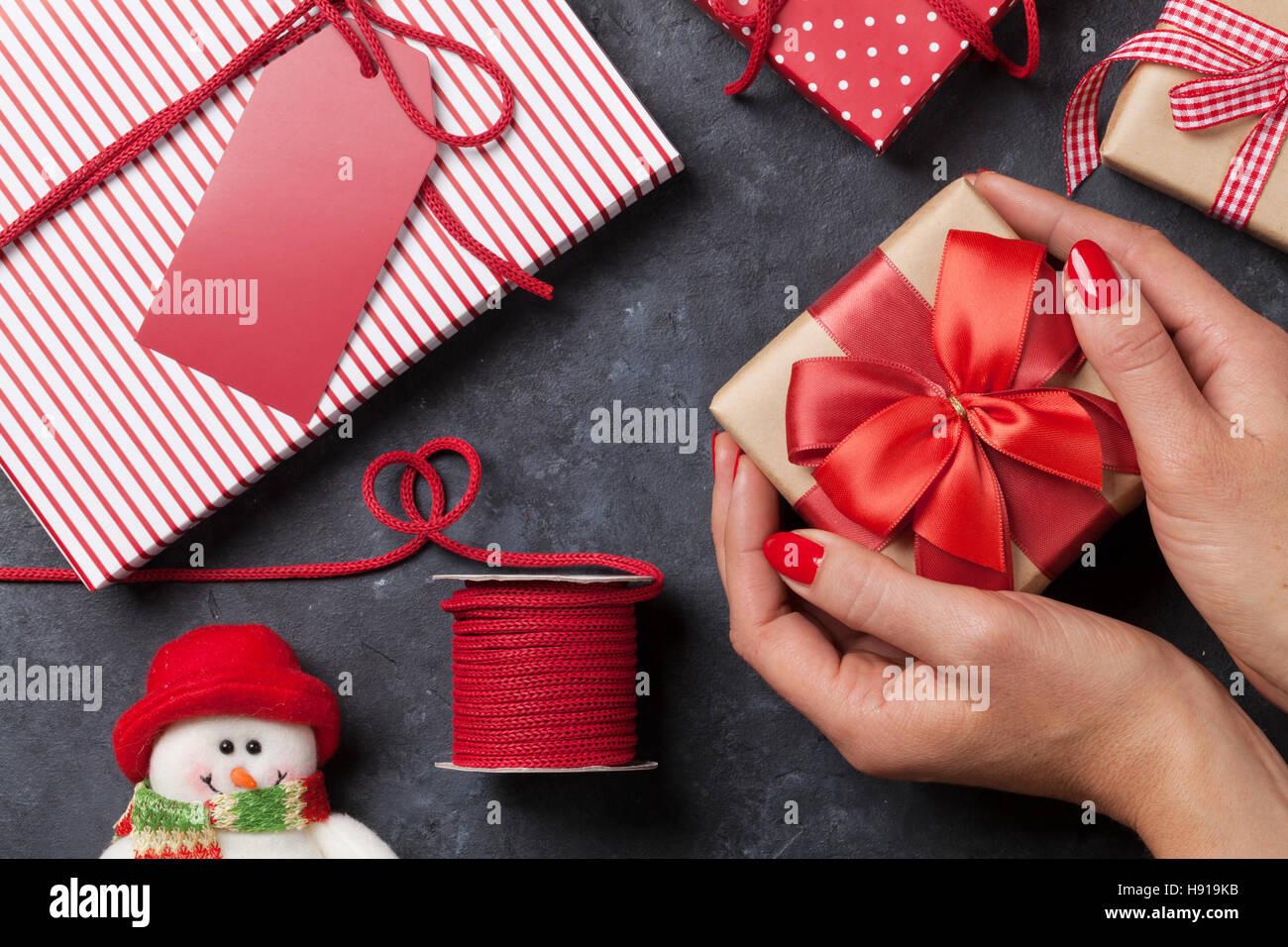 Weibliche Hände halten Weihnachtsgeschenk über Steintisch. Ansicht ...