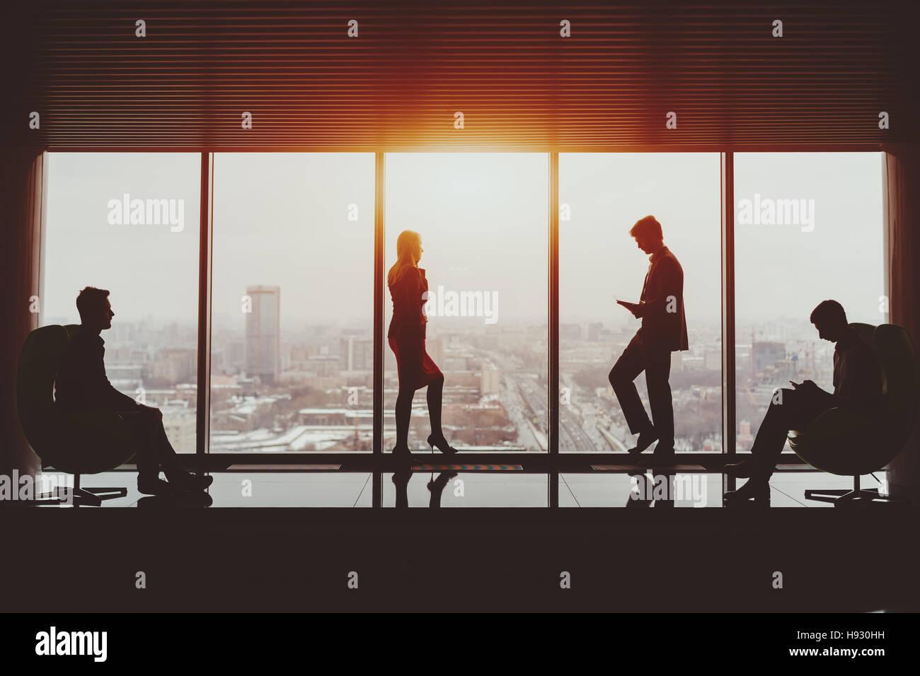 Silhouetten von Geschäftsmann und Geschäftsfrau Stand in der Nähe der Fenster der Wolkenkratzer und Stockbild