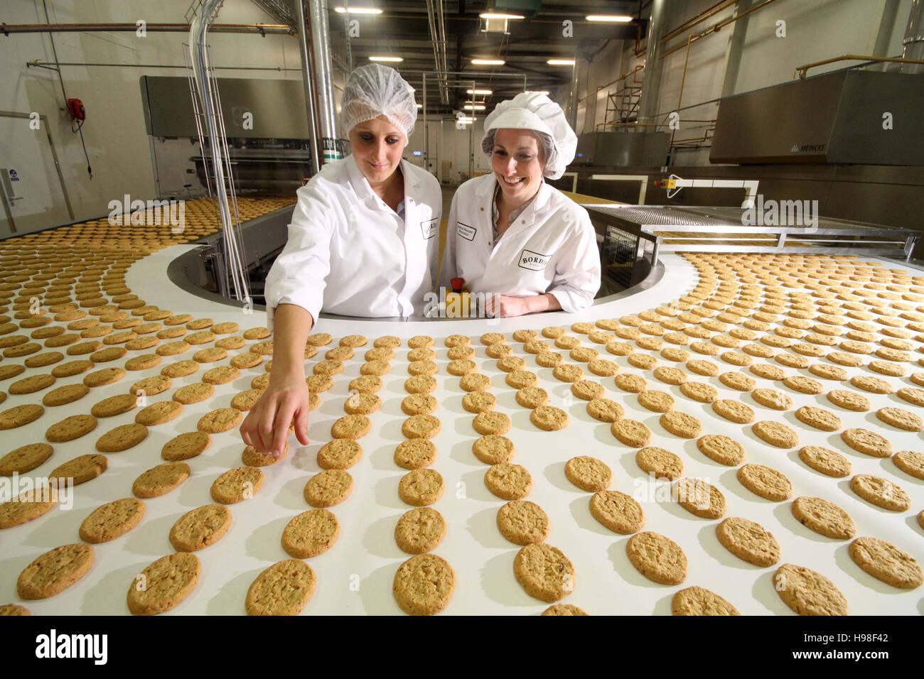 Produktionslinie mit Keksen und Fabrikarbeiter Stockbild