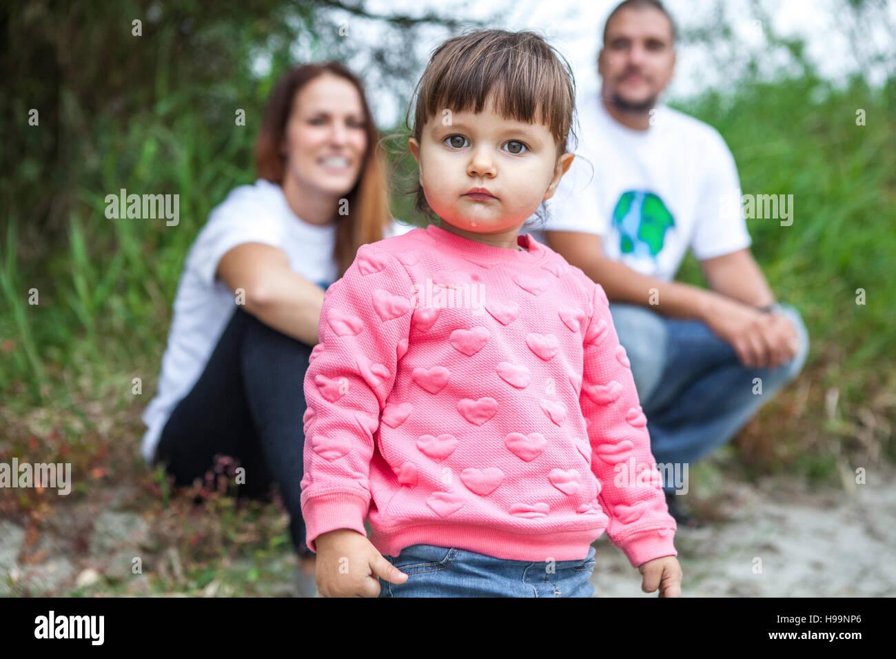 Kleinkind Mädchen mit Eltern im Hintergrund Stockbild