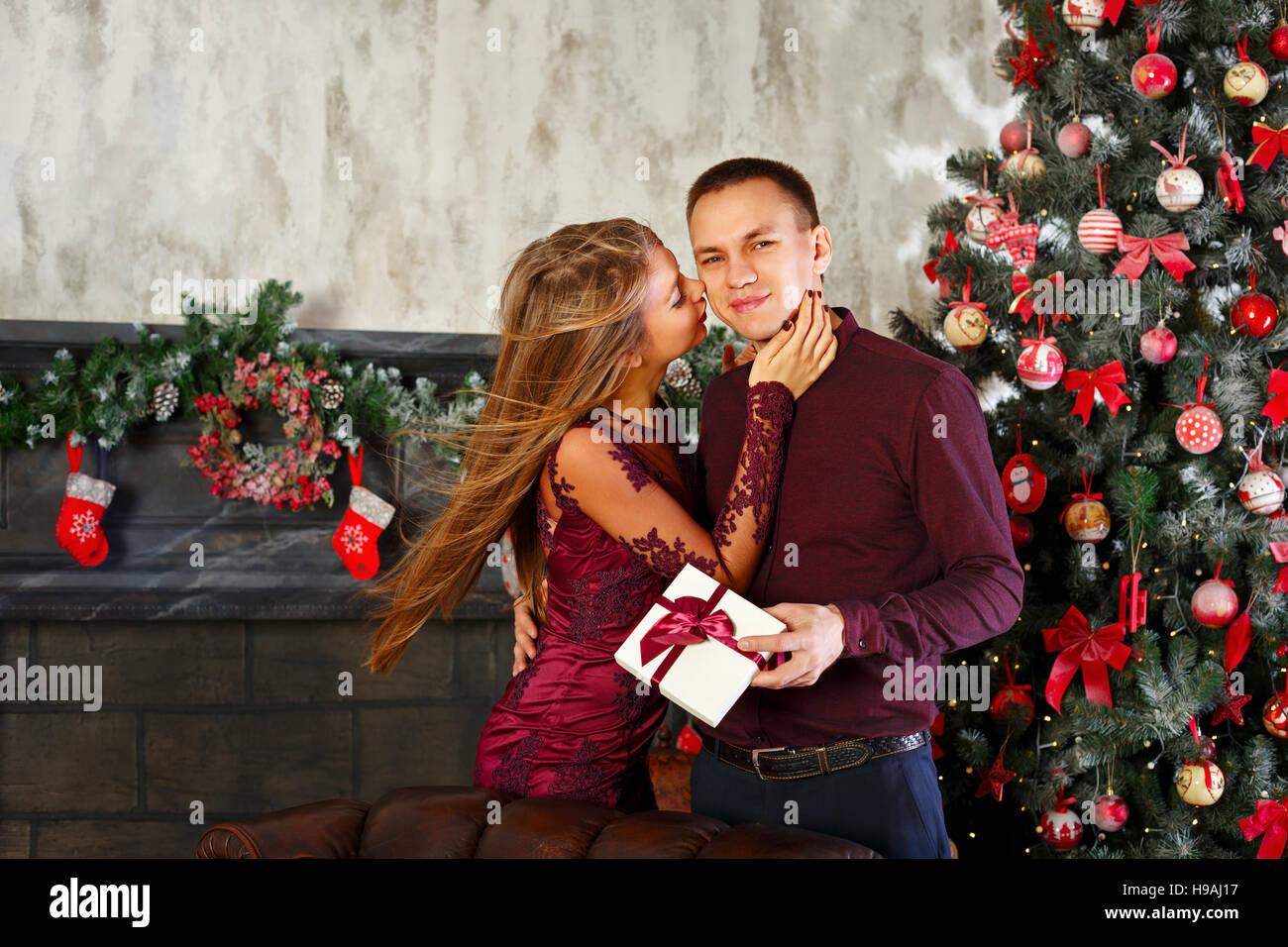 Liebespaar und Weihnachten. Mädchen gibt einen Kuss und ein ...