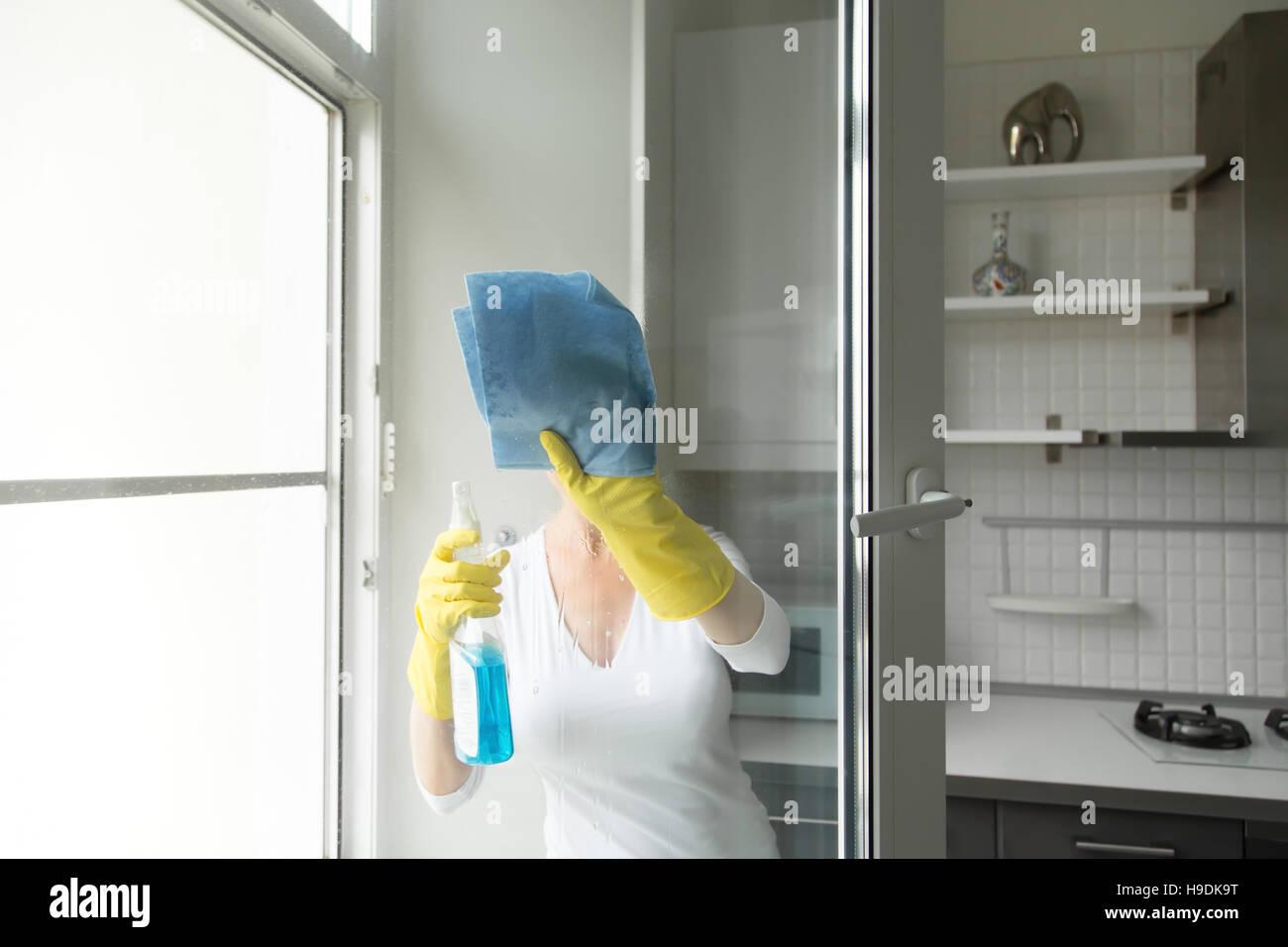 Junge Frau, die die Fenster putzen Stockbild