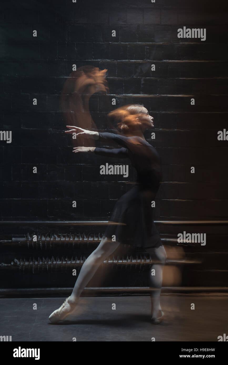 Anmutige Tänzerin Aufwärmen auf dem dunklen Hintergrund Stockbild