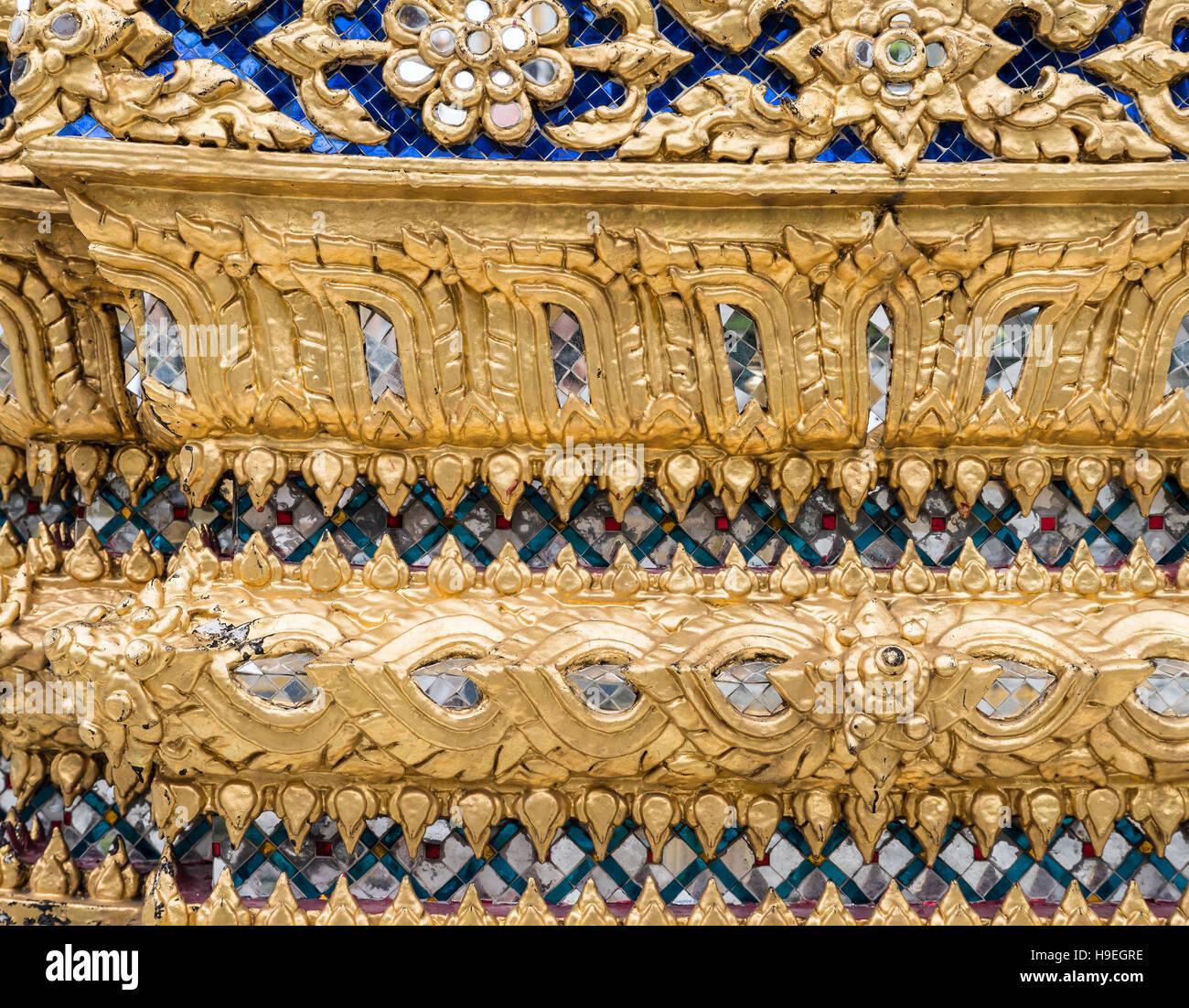 Goldene Blumenmuster mit Glasmosaik an der Kirchenmauer im thailändischen Tempel. (Nicht erforderlich öffentlicher Stockbild