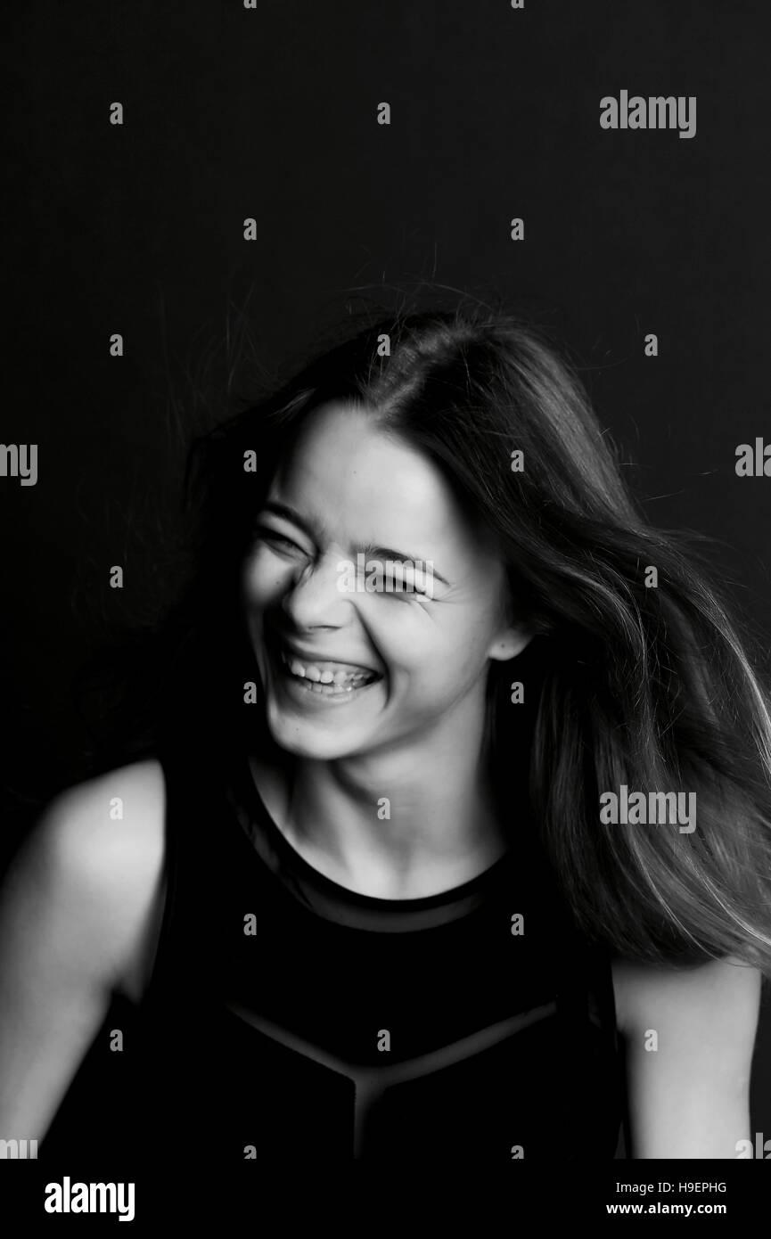 Emotionales Porträt eines schönen Mädchens mit langen Haaren. Breites Lächeln Stockbild