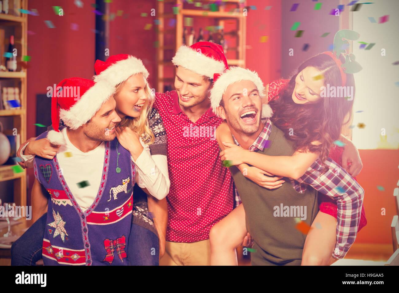 Zusammengesetztes Bild der fröhlichen Männer tragen Weihnachten geben Frauen Huckepack tragen Stockbild