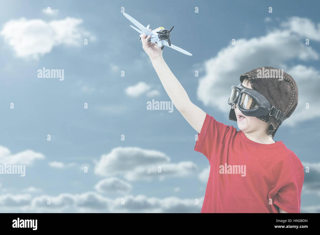 Zusammengesetztes Bild des jungen spielen mit Spielzeugflugzeug Stockbild