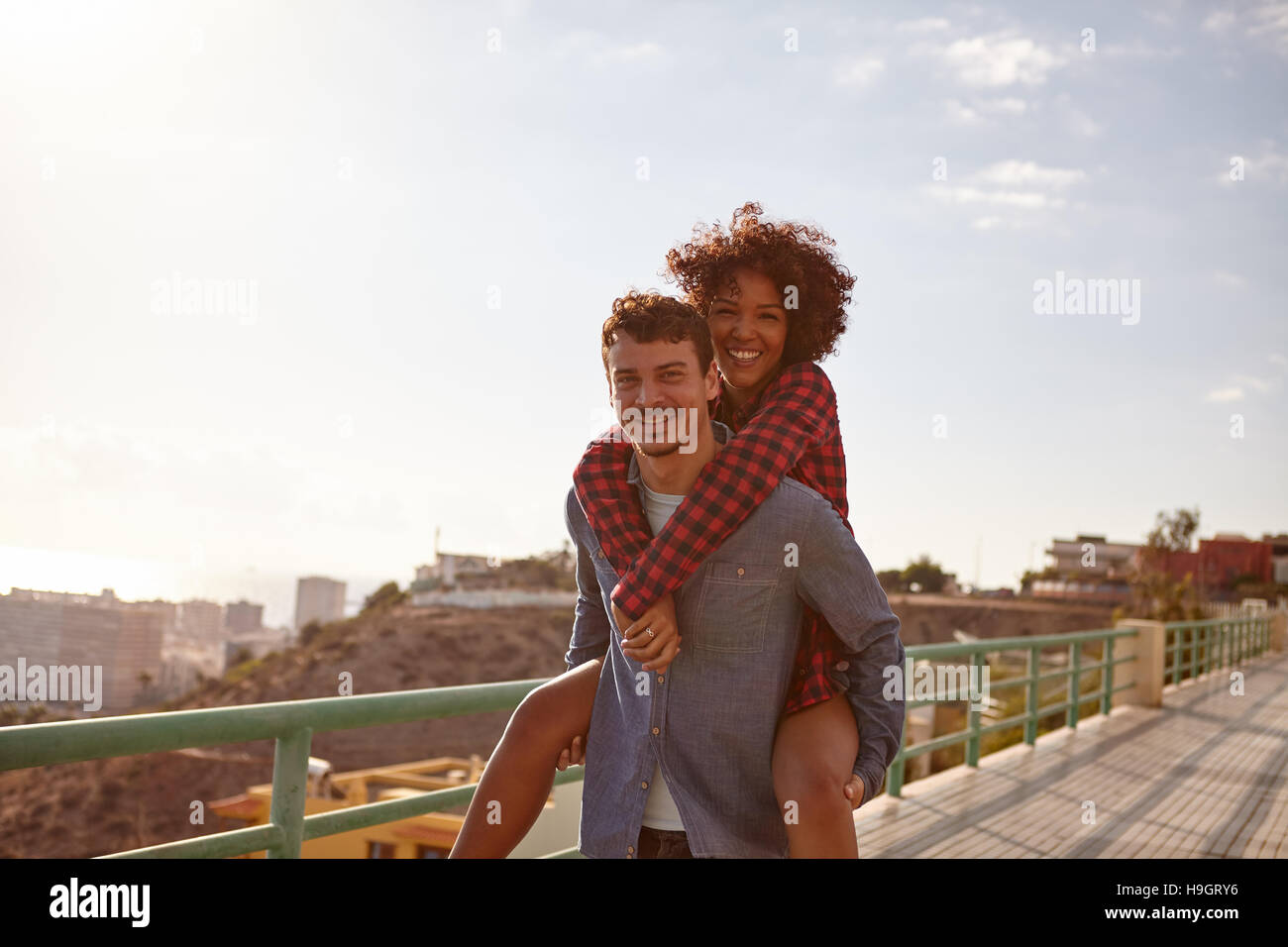 Glücklich Jüngling seine Freundin eine Huckepack geben, wie sie toothy Lächeln mit ihre Arme um seinen Hals lächelt Stockfoto