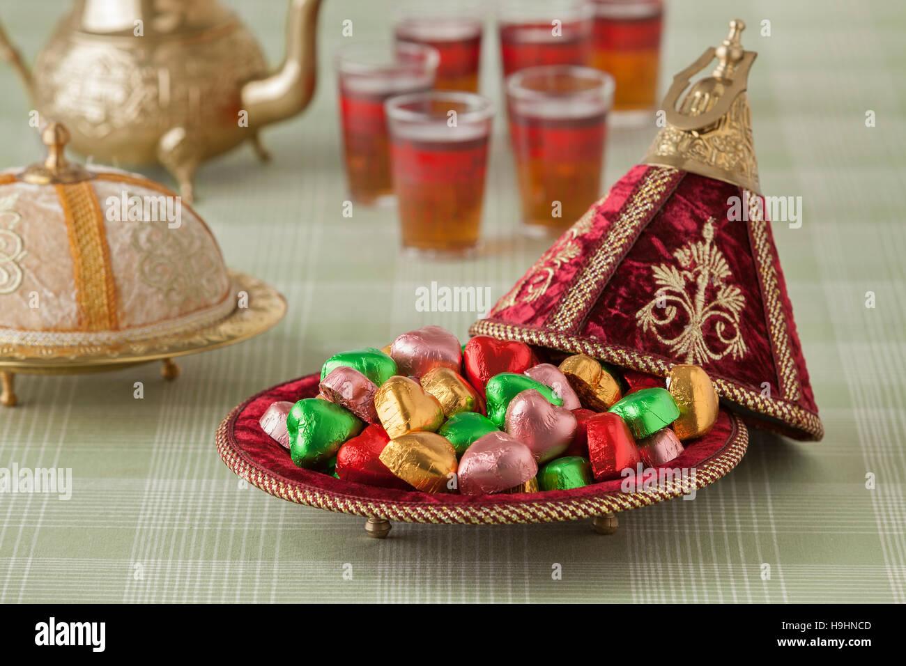Marokkanische festliche Süßigkeiten in eine rote Tajine und Tee Stockbild