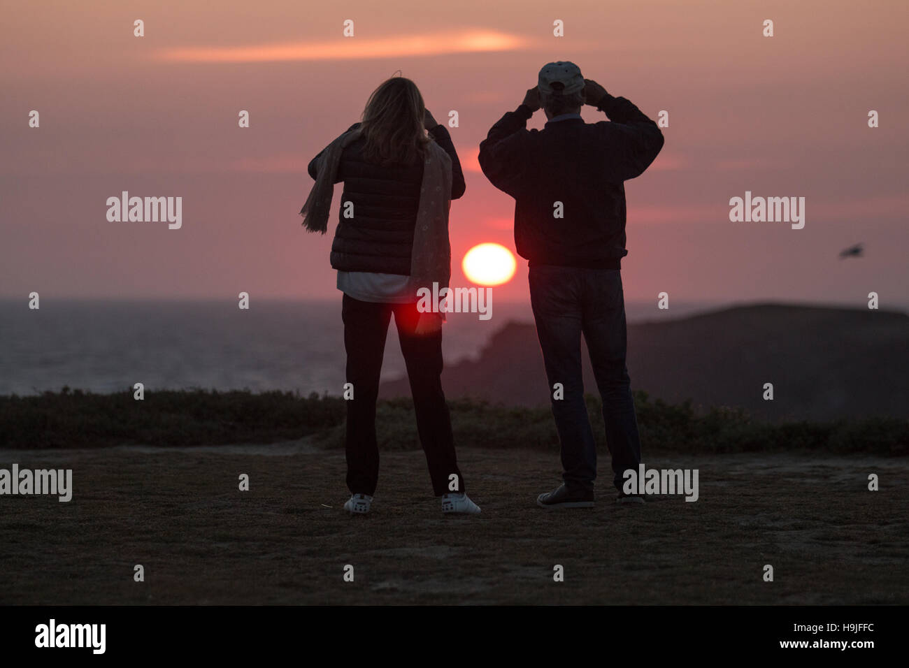 Ein paar schätzen einen schönen Sonnenuntergang am Port Coton Stockbild