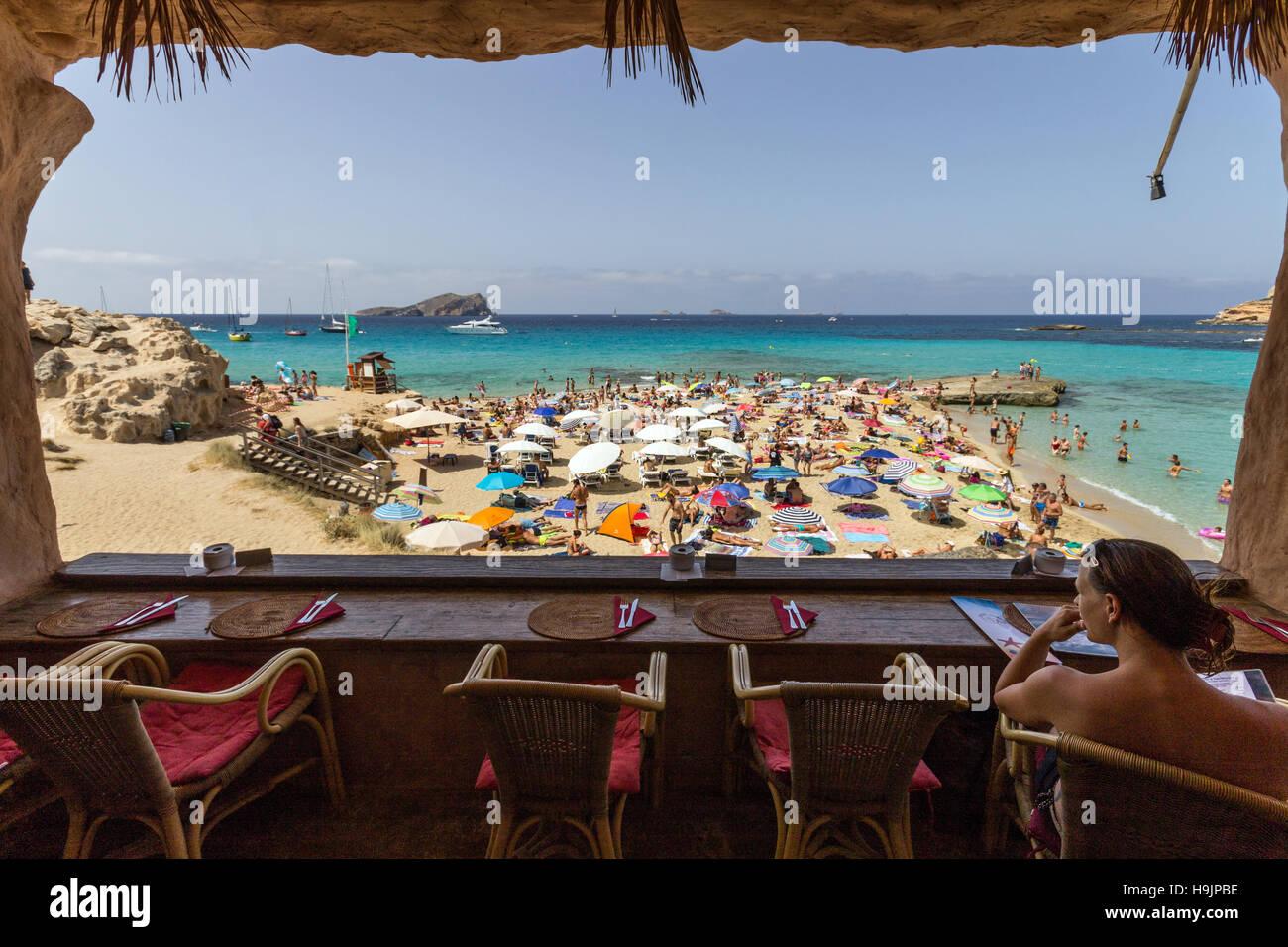 Spanien, Balearen, Ibiza, Strand Cala Comte, Frau sitzt im Café Stockbild
