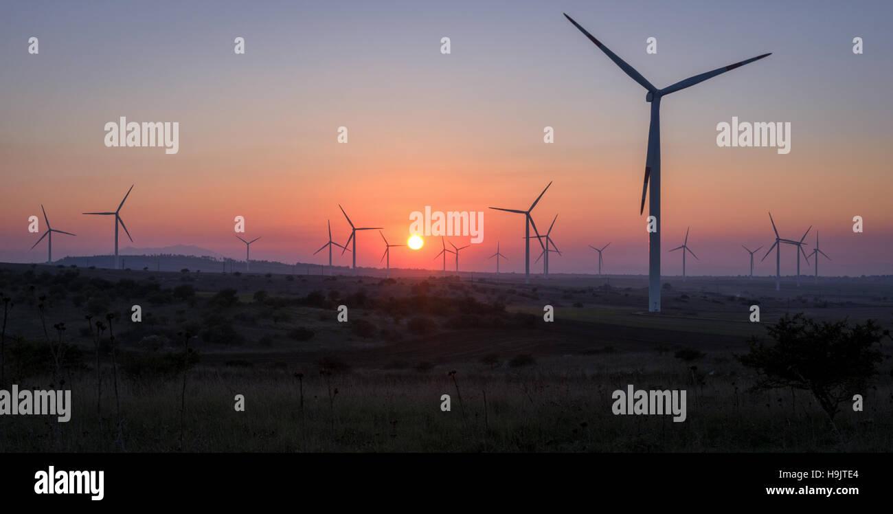 Windenergieanlagen bei Sonnenuntergang - erneuerbare Energie-Konzept Stockbild