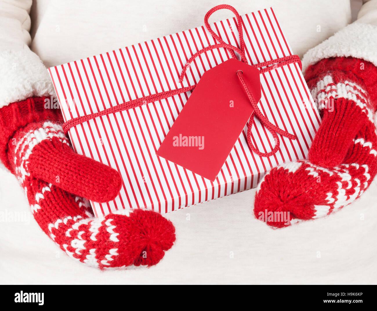 Weibliche Hände halten Weihnachtsgeschenk in rote Handschuhe ...