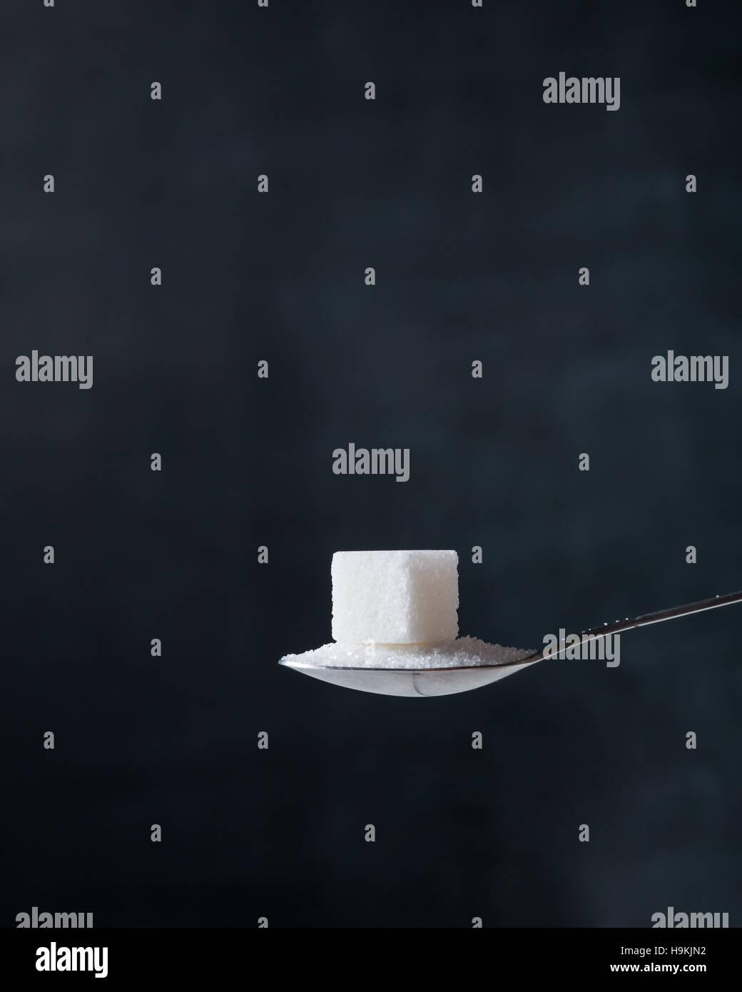 Stück Würfelzucker und Kristallen in einem silbernen Teelöffel auf dem dunklen Hintergrund. Stockbild