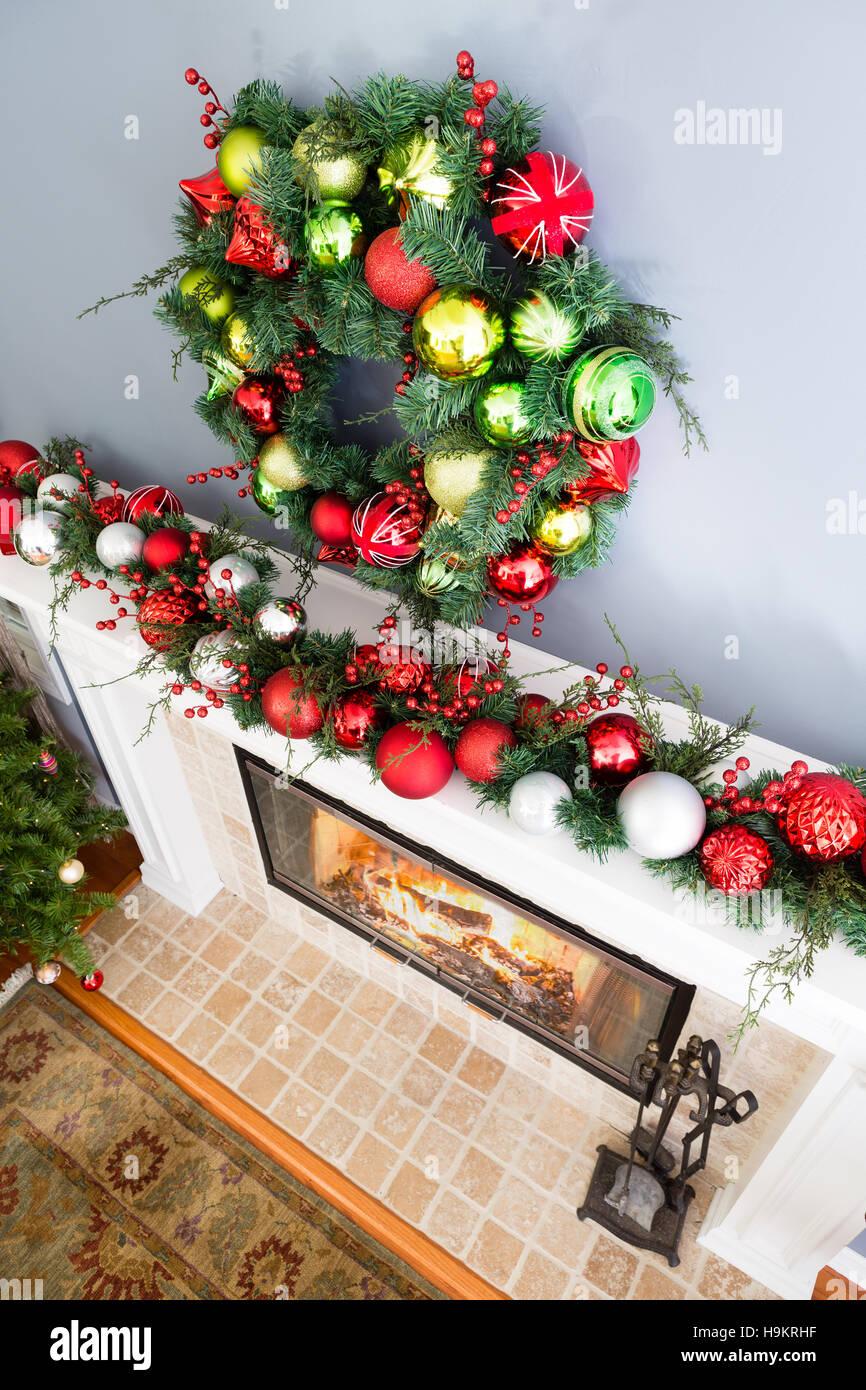 Traditionelle Bunte Weihnachten Kranz Hängen über Dem Kamin Und Dem Kaminsims  Dekoriert Mit Einem Kranz Von Roten Und Weißen Kugeln Mit Dunkelgrünem Laub