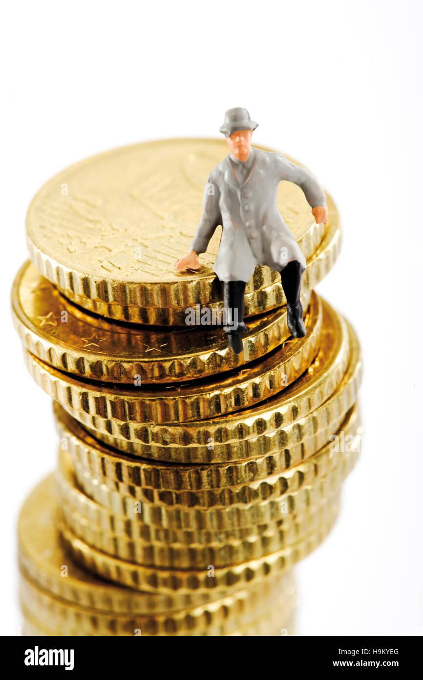 Figur auf einem Stapel von Münzen, Mann trägt einen Regenmantel Stockbild