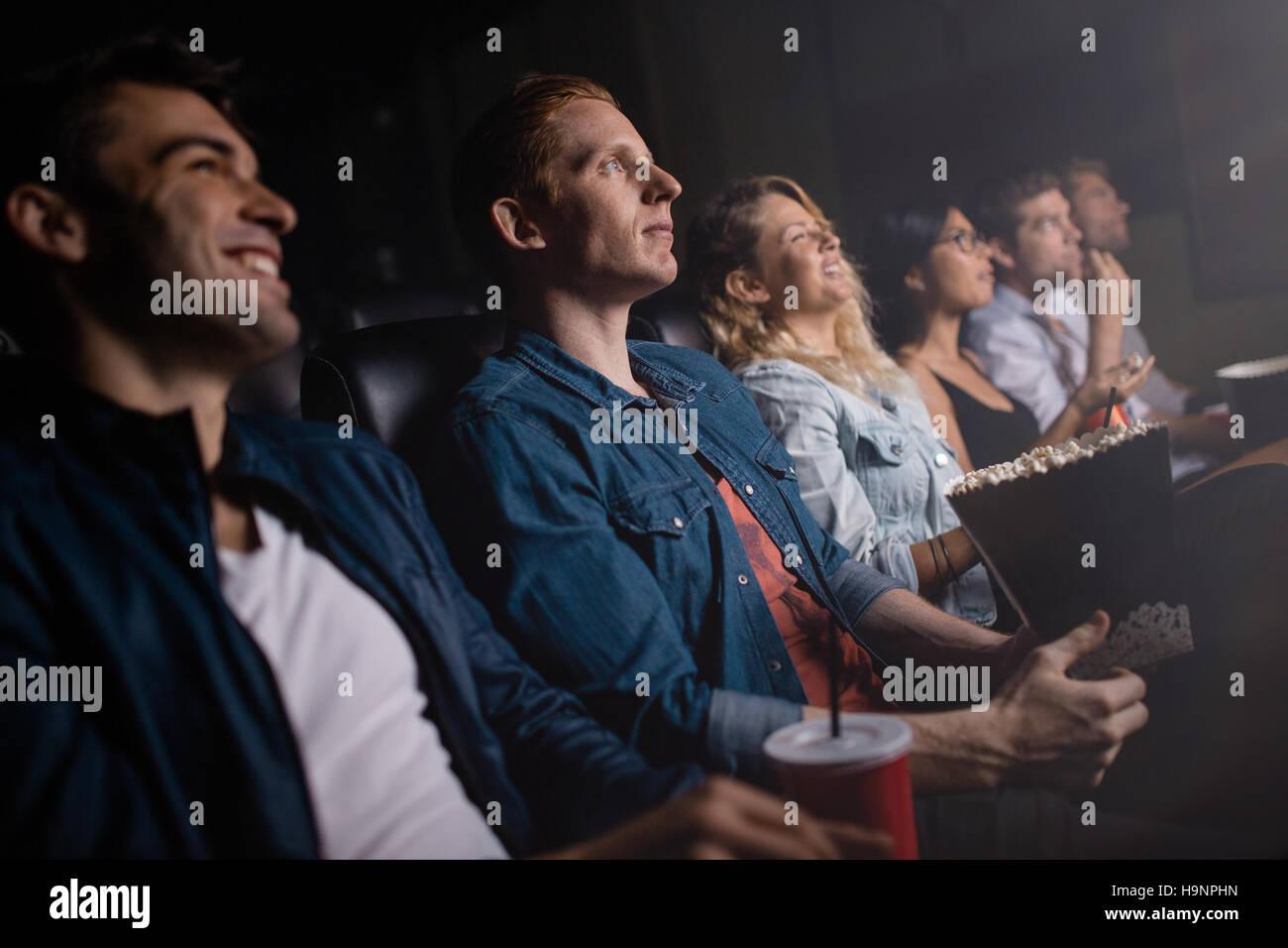 Gruppe von Personen in Theater, Film. Junger Mann mit Freunden im Kino. Stockbild