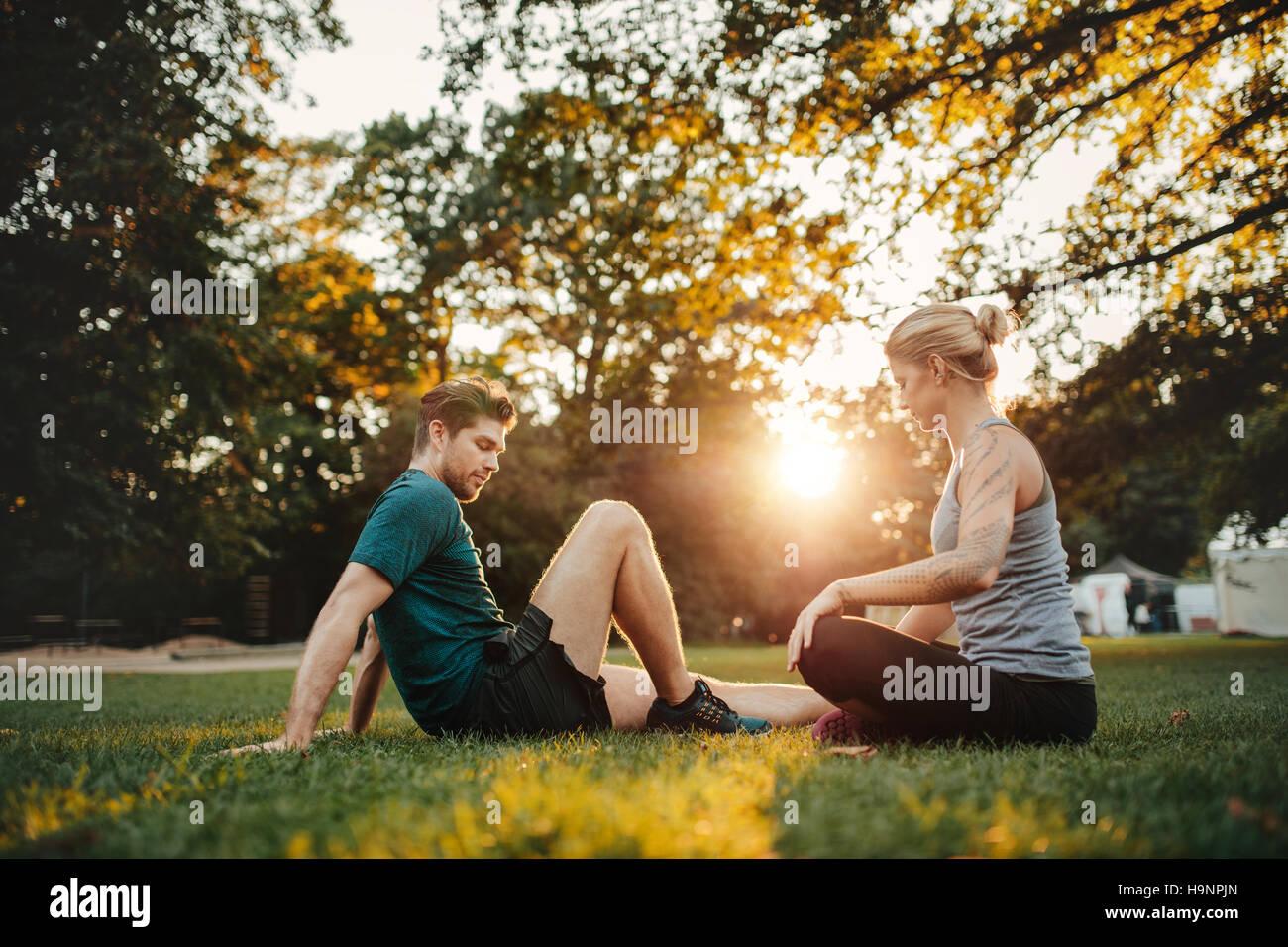 Schuss von junges Paar im Park sitzen und arbeiten. Mann und Frau im Park Morgen trainieren. Stockbild