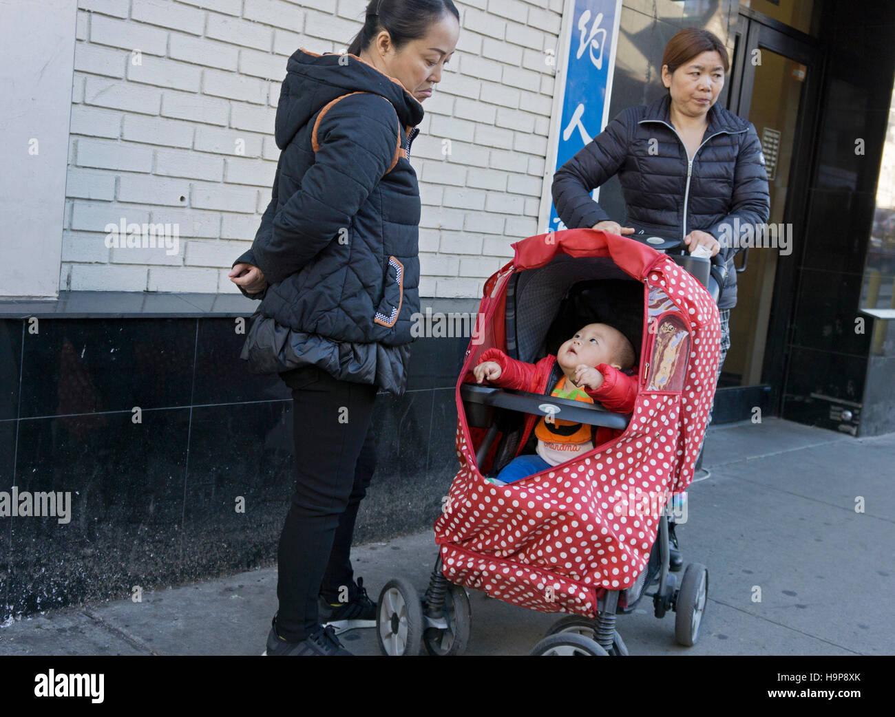 Zwei asiatische Frauen und ein Kind ansprechbar vom Main Street in Chinatown, Downtown Flushing, Queens, New York Stockfoto