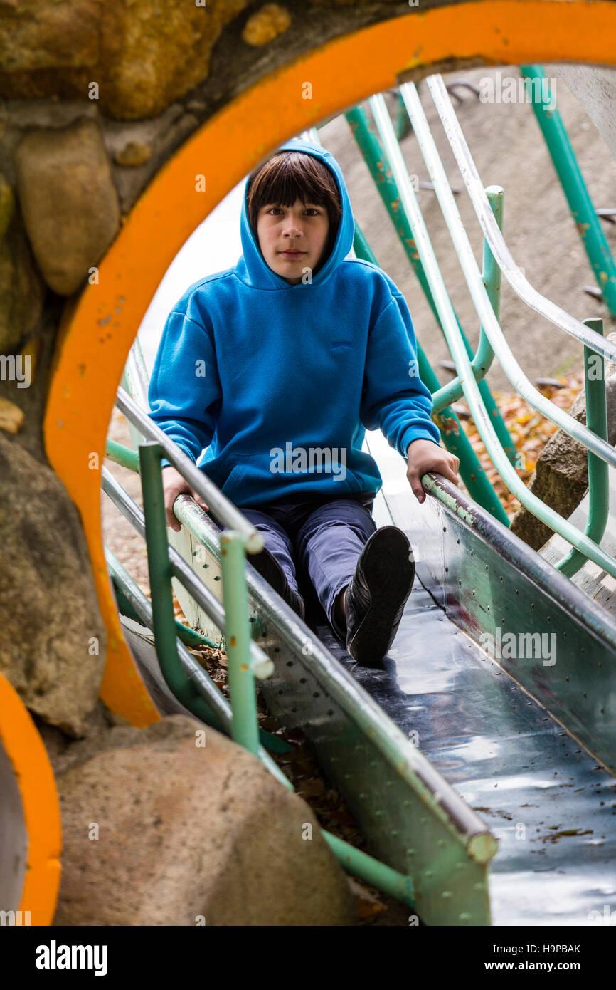 Japan, Akashi. Kazki, frühe Teenager Kaukasischen junge, 13-14 Jahre alt, in Blau hoodie Gleiten auf Folie Stockbild