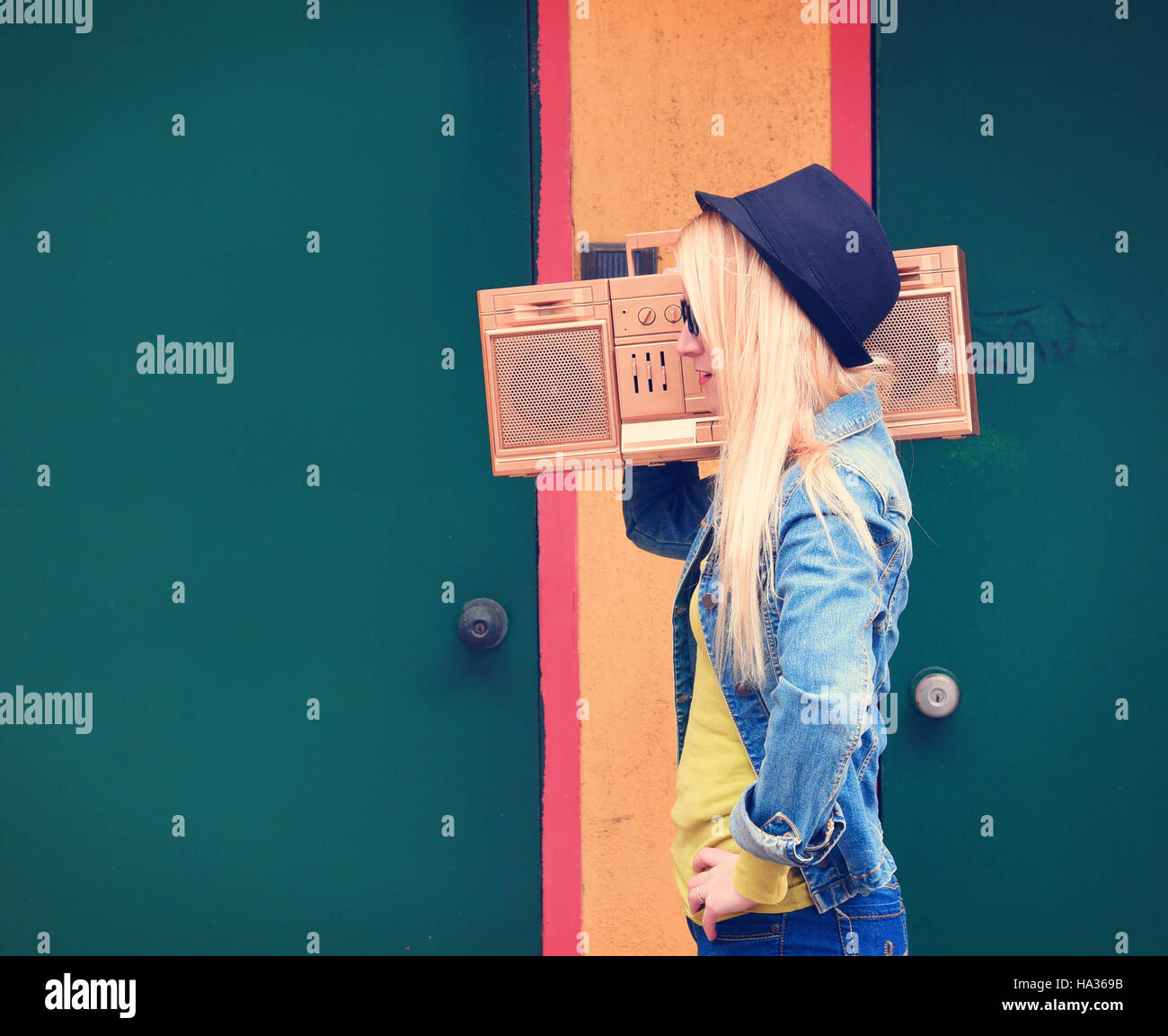 Eine blondes Hipster Mädchen mit Brille hört ein Vintage gold Boombox Radio mit Lautsprecher für eine Musik-Entertainment-Konzept. Stockfoto